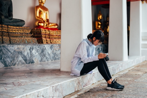 De aziatische vrouwenreiziger zit en controleert foto in camera dichtbij het standbeeldachtergrond van boedha