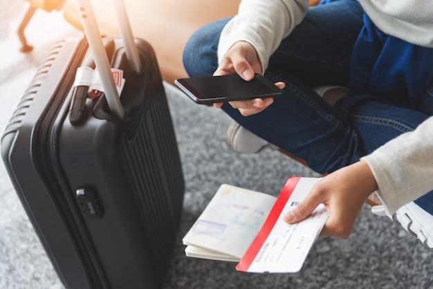 De aziatische vrouwenreiziger zit en gebruikt smartphone op de luchthaven.
