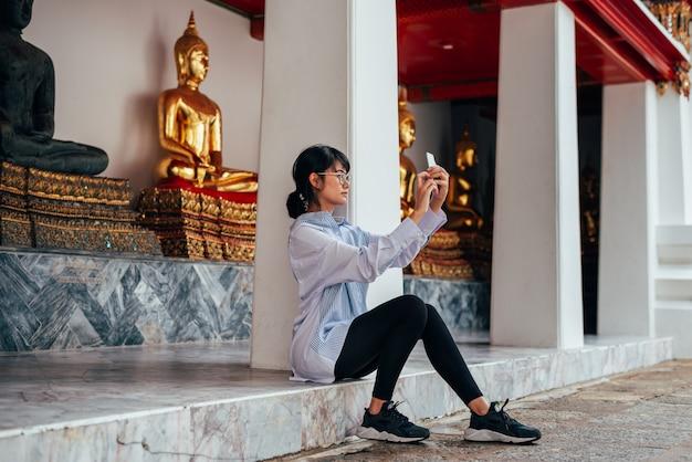 De aziatische vrouwenreiziger zit en gebruikt smartphone selfie zelf met een oude het standbeeldachtergrond van boedha