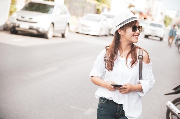 De aziatische vrouwentoerist controleert het texting van smartphone op straat, gebruikend mobiele telefoonapp om kaart online te controleren.