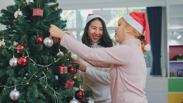 De aziatische vrouwenvrienden verfraaien kerstboom bij kerstmisfestival. het vrouwelijke tiener gelukkige glimlachen viert samen de vakantie van de kerstmiswinter samen in woonkamer thuis.