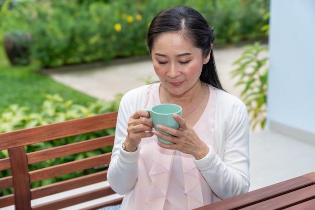 De aziatische vrouwenzitting met kop van koffie tuiniert thuis