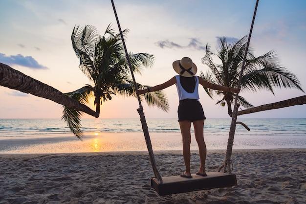 De aziatische vrouwenzomer ontspant op schommeling in strand bij de zomer van zonsondergangthailand
