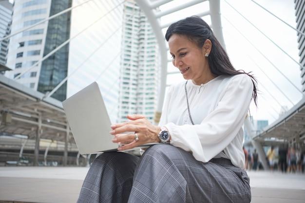 De aziatische werkende vrouw gebruikt laptop terwijl in openlucht het zitten.