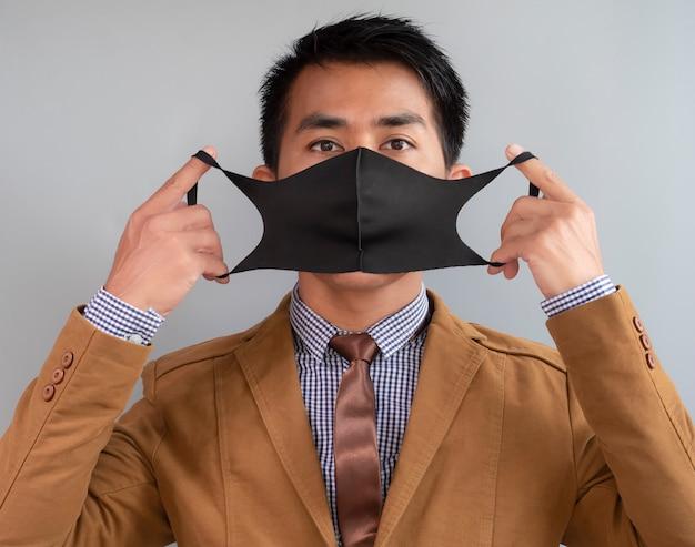 De aziatische zakenman draagt masker dat tegen coronavirus probeert te beschermen