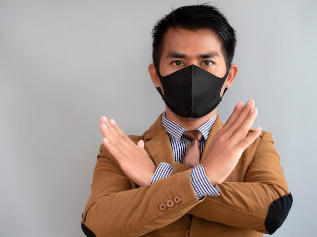 De aziatische zakenman toont dwarshandteken en draagt masker proberend om tegen coronavirus te beschermen