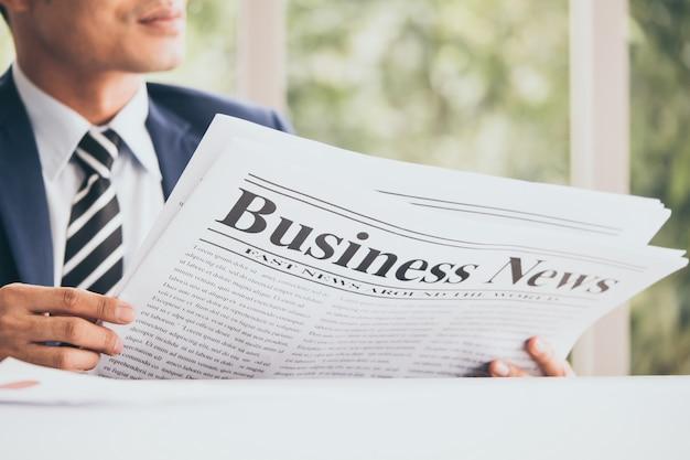 De aziatische zakenman zit en leest nieuws van een krant op het kantoor.