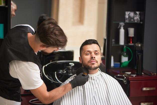 De baard van de mannelijke kapper verzorgende cliënt met borstel.