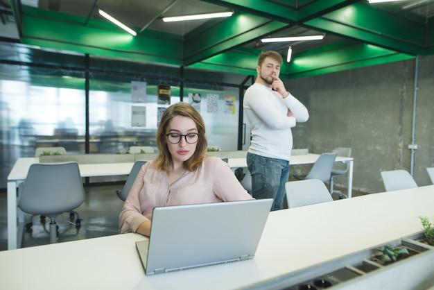 De baas van de man minacht naar een vrouw die op de werkplek op een laptop werkt.