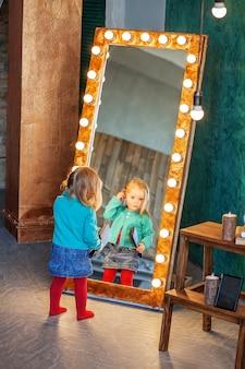 De baby die haar kamt bij de spiegel