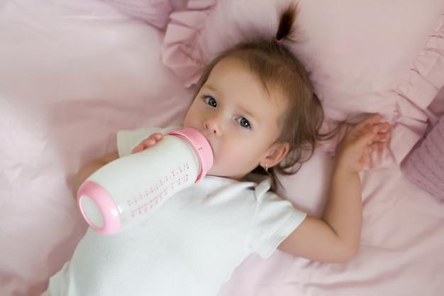 De baby drinkt melk uit een fles