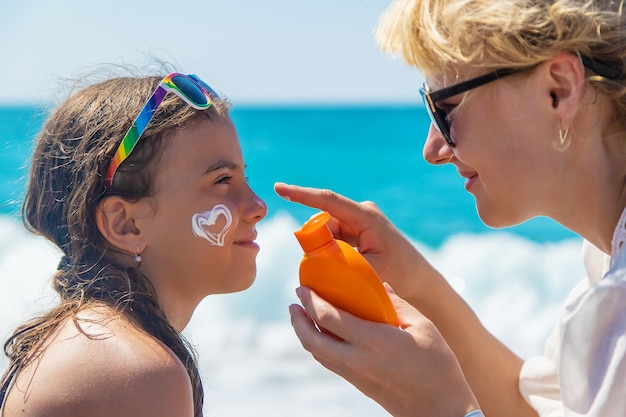 De baby en de moeder smeren zonnebrandcrème op hun gezicht. selectieve aandacht.