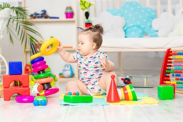 De baby haalt de piramide op, het kind speelt thuis in de crèche