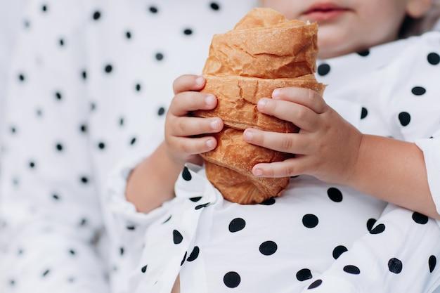 De baby houdt een croissant in zijn hand