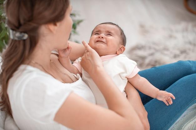 De baby huilt in de armen van zijn moeder. een vrouw probeert haar kleine kind te kalmeren.