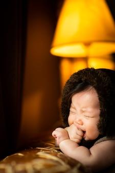 De baby huilt tegen de bruine bank