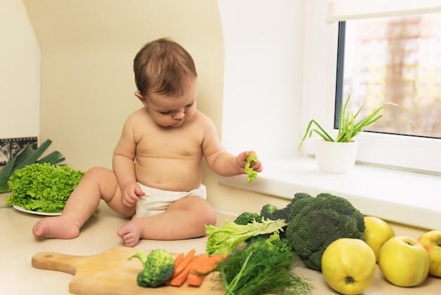 De baby in de luier zit op de keukentafel. een kind speelt en heeft plezier met verse biologische groenten en fruit.