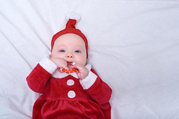 De baby in een santahoed ligt op een witte achtergrond, knaagt aan een stuk speelgoed.