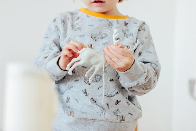 De baby in pyjama's die een kerstmisstuk speelgoed herten houden, sluit omhoog