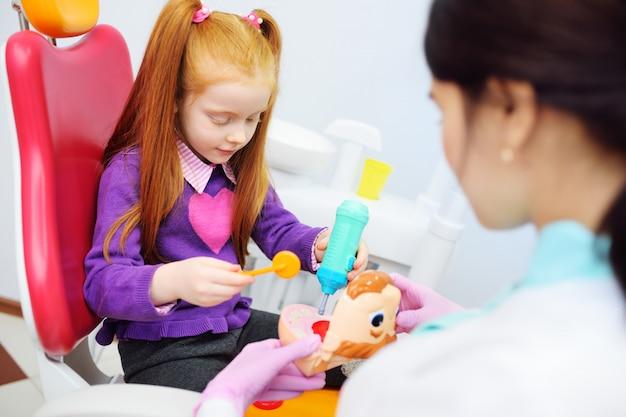 De baby is een klein roodharig meisje en een vrouwelijke pediatrische tandarts speelarts met stuk speelgoed tandinstrumenten die als tandvoorzitter zitten.