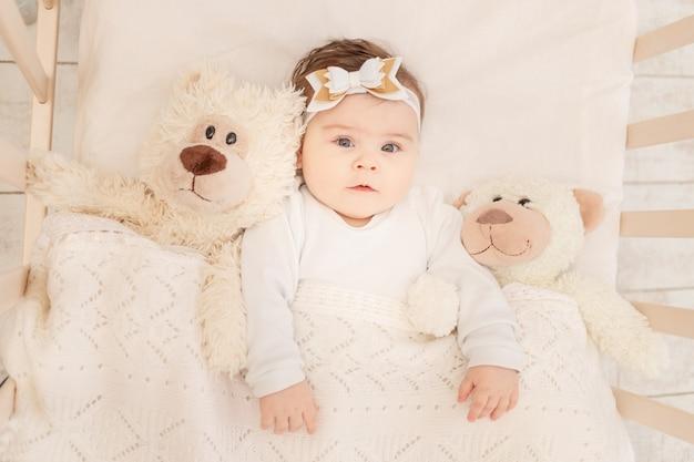 De baby is zes maanden oud in een wieg in een wit rompertje met een teddybeer