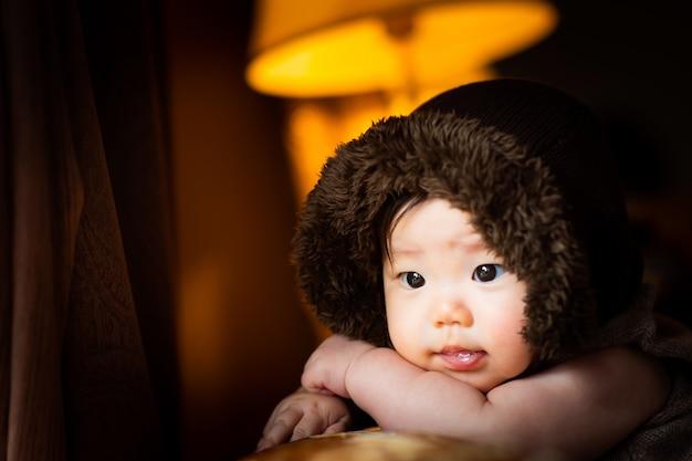 De baby kijkt met een glimlach naar de voorkant met zijn handen samen