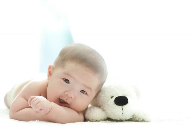 De baby lacht vooraan op een wit bed met een witte achtergrond.