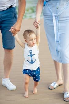 De baby leert lopen door de eerste stappen te nemen om de handen van ouders, moeders en vaders in de zomer op blote voeten vast te houden