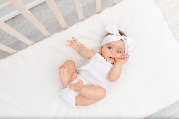De baby ligt in de wieg in de kinderkamer op een wit bed en zuigt aan zijn vinger
