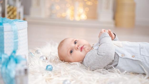 De baby ligt op een donzig tapijt met kerstversieringen