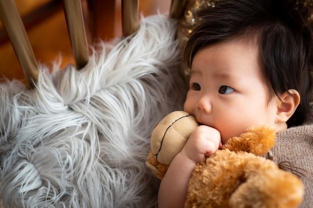 De baby ligt op het tapijt en zit op de pop