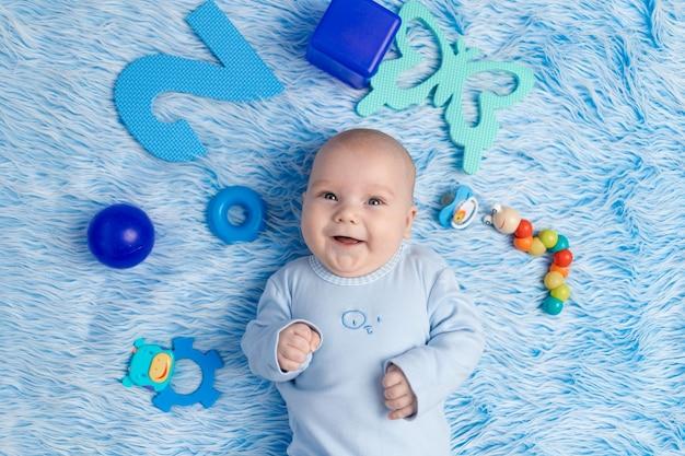 De baby ligt thuis op een blauwe mat tussen het speelgoed, het concept van ontwikkeling en games