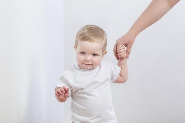 De baby neemt de eerste stapjes terwijl hij mama's hand vasthoudt