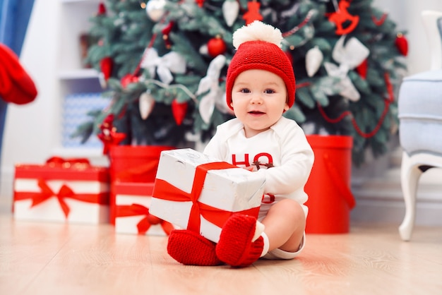 De baby pakt giftdozen met kerstmisdecoratie uit, gekleed als kerstman, bokeh lichten, het concept van de de wintervakantie