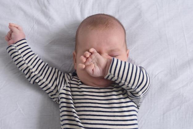 De baby rekt zich uit tijdens het slapen