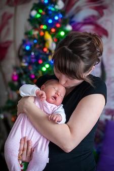 De baby slaapt in de armen van zijn moeder