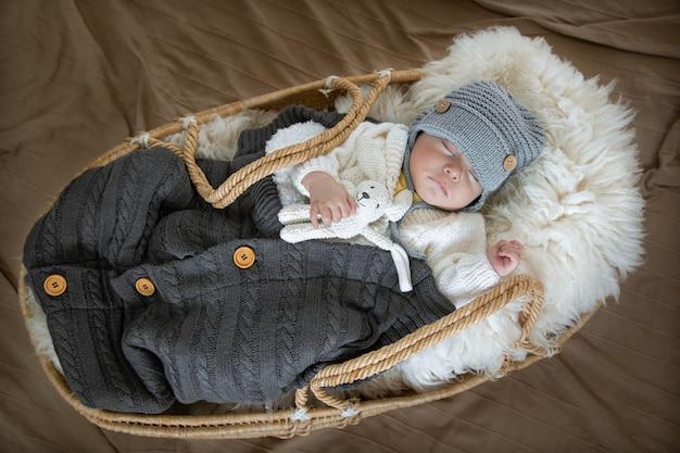 De baby slaapt in een rieten wieg in een warme gebreide muts onder een warme deken met een speeltje in het handvat van dichtbij.