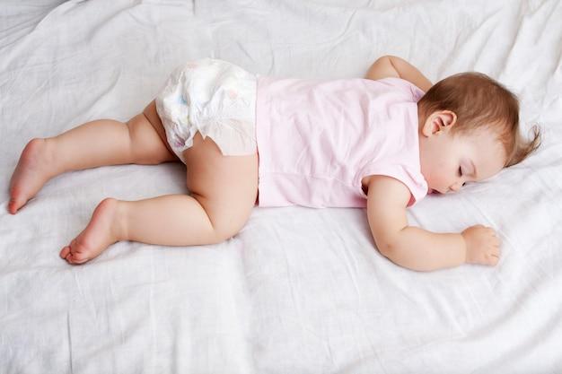 De baby slaapt op zijn buik op een wit bed