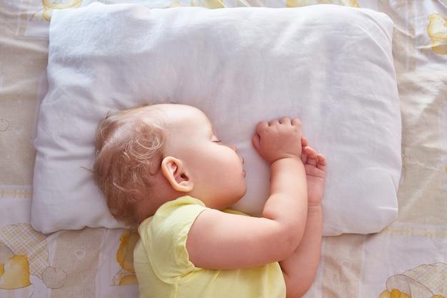 De baby slaapt op zijn zij op een wit kussen. bovenaanzicht.