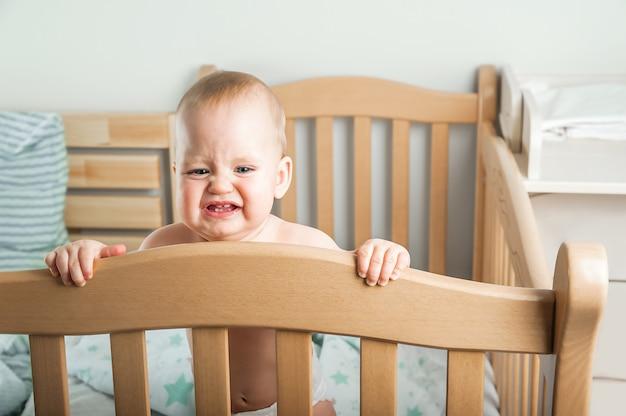 De baby van 8 maanden oud huilt op bed slaap van een baby in een wieg die uit zichzelf in slaap valt en koliek krijgt doorkomende tandjes