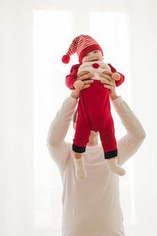 De baby van de jonge mensenholding in kerstmiskruippakje