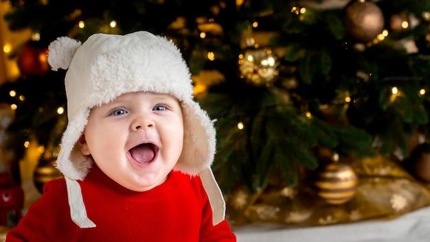 De baby van kerstmis glimlacht. schattig klein meisje in een rode jurk en een witte hoed drukt emoties uit. kerst concept met klein kind