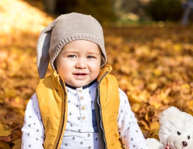 De baby van vooraanzichtsmiley met stuk speelgoed in openlucht