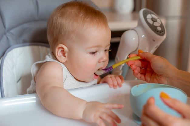 De baby zit in een hoge stoel in de keuken waar zijn moeder pap aan het voeren is