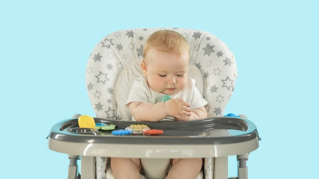 De baby zit op een hoge stoel en speelt met speelgoed