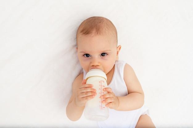 De babyjongen 8 maanden oud ligt consumptiemelk van een fles op het bed in de kinderdagverblijf, voedend de baby, babyvoedingconcept