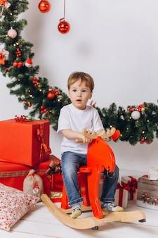 De babyjongen die van de zuigeling thuis in kerstmisavond speelt. vakantie decoraties, oudejaarsavond met kleurrijke lichten zijn op de achtergrond