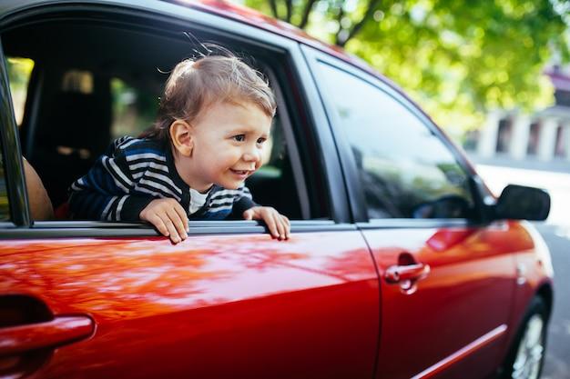 De babyjongen in de auto die werpt venster kijken.