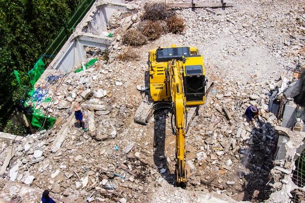 De backhoe machines werken op site sloop van een oud gebouw werknemers.