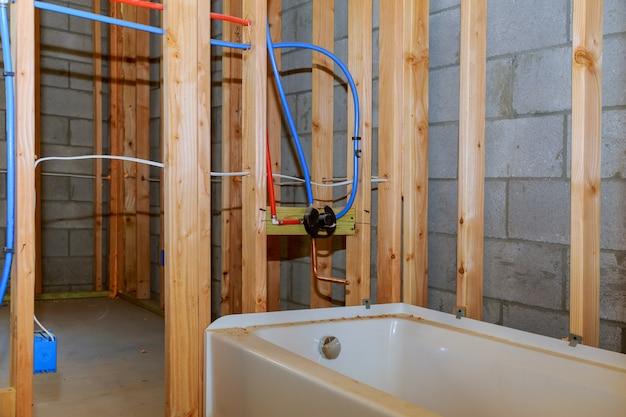 De badkamersvernieuwing die het werk van de vloerloodgieterij toont die installatie van pijpen voor water voor nieuwe gebouwen verbindt